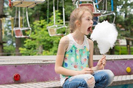 Photo pour Petite fille avec un grand bâton de fil dentaire de bonbons ouvrant sa bouche large alors qu'elle se prépare à prendre une bouchée du sucre filé à une foire d'été - image libre de droit