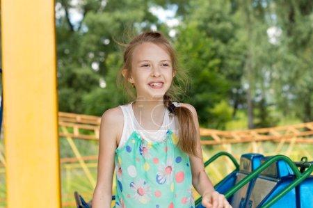 Photo pour Bonne petite fille à la foire souriant dans l'anticipation alors qu'elle se prépare à prendre place sur l'une des levées - image libre de droit