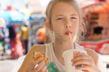 Young girl sipping a soda in a street cafe