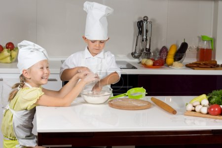 Photo for Two cute children making homemade pizza dressed in white chefs apron and hat working at the counter mixing ingredients for the dough with a pile of fresh vegetables alongside - Royalty Free Image