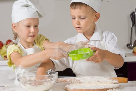 Two children making pastry for pizza bases