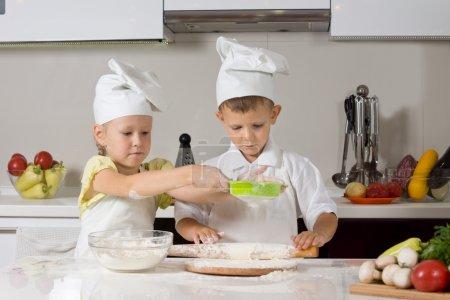 Photo pour Mignon petit garçon et fille, vêtus d'uniformes de cuisiniers cuisson ensemble dans le travail de la cuisine une équipe faisant et rouler la pâte pour les bases de pizza - image libre de droit