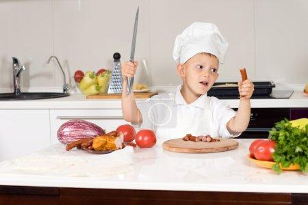 Photo pour Petit garçon s'amusant à faire des pizzas maison brandissant un gros couteau dans la cuisine d'une main et une saucisse épicée qu'il a hachée de l'autre - image libre de droit
