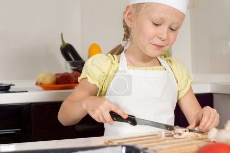 Smiling young girl slicing mushrooms for dinner