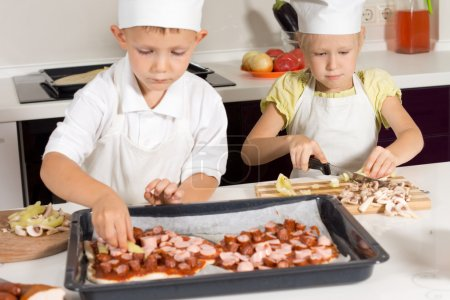 Photo for Cute Little Kids in Chef Attire Making Tasty Pizza in the Kitchen. - Royalty Free Image