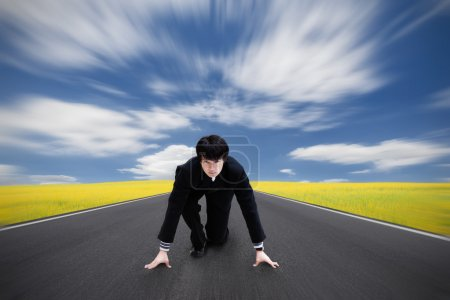 Young asian businessman kneeling as if about to start a race