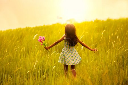 Photo for Little girl running on meadow with sunset - Royalty Free Image