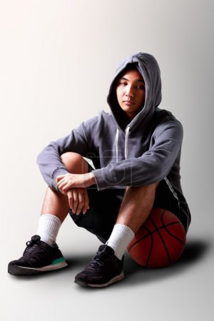 Sad teenager boy sitting on basketball