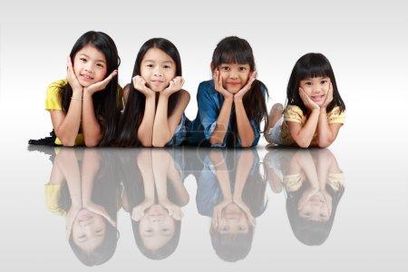 Foto de Cuatro chicas asiáticas poco felices tirado en el piso, aislado en blanco con sombras - Imagen libre de derechos