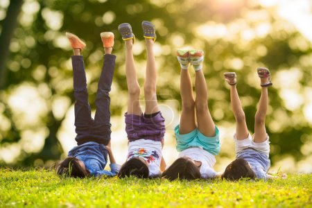Photo for Group of happy children lying on green grass outdoors in spring park - Royalty Free Image
