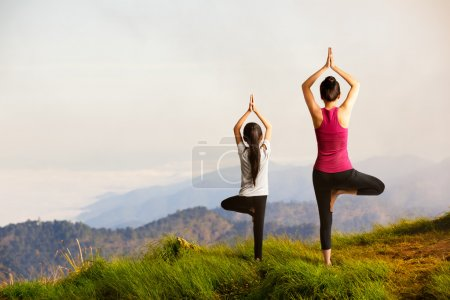 Photo for Mother and daughter doing yoga at top of mountain - Royalty Free Image