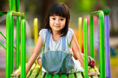 Malá Asijská dívka sedí na snímku u hřiště