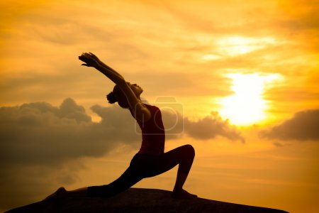 Photo for Young asian woman practicing yoga warrior pose at sunset - Royalty Free Image