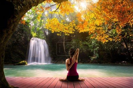 Photo pour Jeune femme dans une pose d'yoga assis près de watefall, vue arrière - image libre de droit