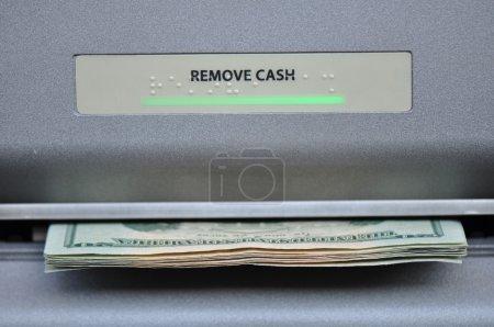 Photo pour Caisse américaine étant dispensés par un maching de guichet automatique de banque, ou atm - image libre de droit