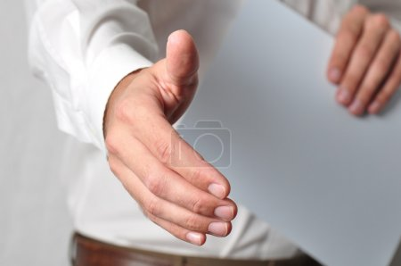Photo for Open handshake and paperwork pose conveying job interview or acceptance - Royalty Free Image