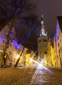 Illuminated street in the Old Town of Tallinn, Estonia at night. Church St. Olaf in background.