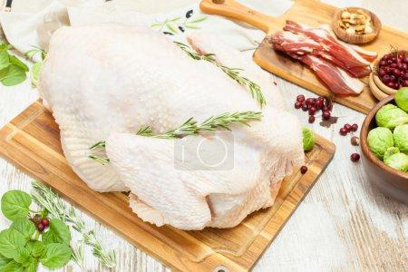Whole raw turkey on wooden cutting board