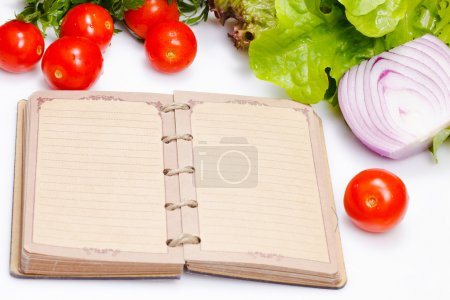 Photo for Notebook for recipes with vegetables or notes of food eaten throughout the day when on a diet - Royalty Free Image