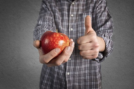 Person holding tasty red apple and showing thumb up.