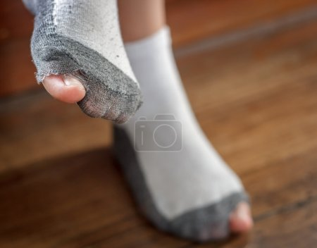 Photo pour Worn out socks with a hole and toes sticking out of them on old wooden floor . - image libre de droit
