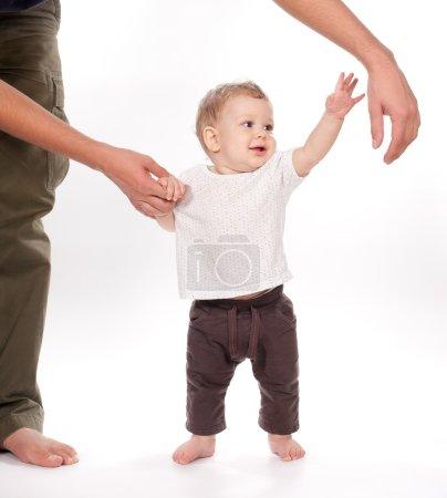 Photo pour Bébé faire les premiers pas avec l'aide du père sur fond blanc - image libre de droit