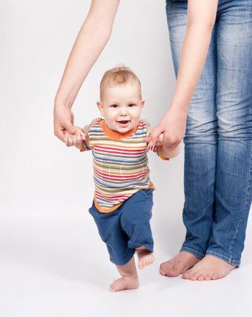 Photo pour Bébé faire les premiers pas avec l'aide de la mère sur fond blanc - image libre de droit