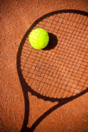 Tennis ball with racket shadow over