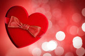 Red heart with red bow, defocused lights on background