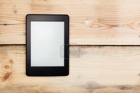 E-book reader or tablet pc on wooden background...