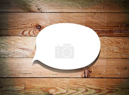 Paper speech bubble on grunge wood background