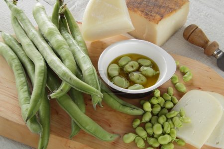 Broad beans with pecorino cheese on white table
