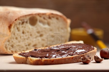 BREAD WITH NUTELLA ON WOODEN TABLE