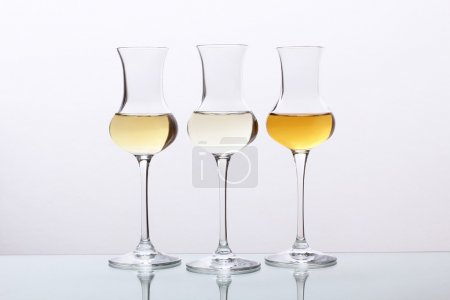 cocktails three glass with tequila or rum or grappa on gray background