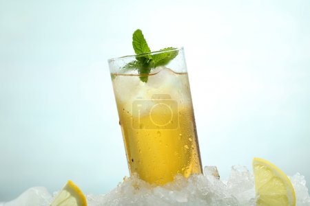 tea with lemon and ice in a glass on green background