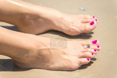 Photo for Woman's foots with a ring on a toe and colored nails on the sunny beach - Royalty Free Image
