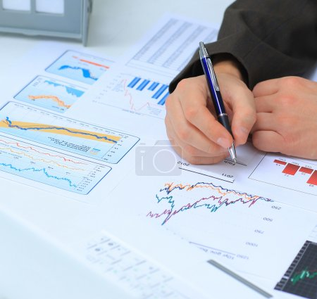 Photo for Businessman analyzing investment charts at his workplace - Royalty Free Image