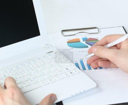 Photo pour Homme d'affaires analysant les graphiques d'investissement sur son lieu de travail - image libre de droit
