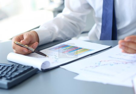 Close-up of graphs and charts analyzed by businessman