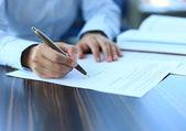 Üzletasszony ül íróasztal sekély összpontosítva aláírás szerződést