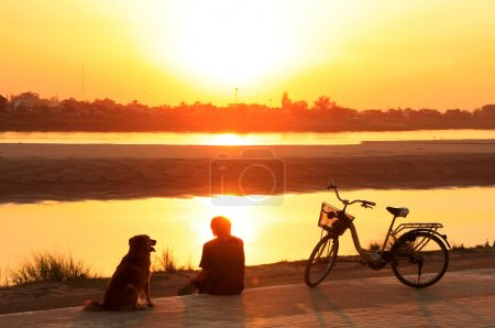 Silhouetted man with a dog watching sunset at Mekong river water