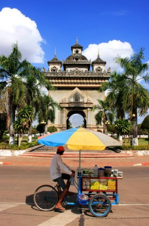 Street food seller on a bicycle in front of Victory Gate Patuxai