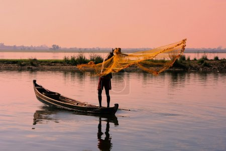 Local man fishing with a net at sunset, Amarapura, Myanmar