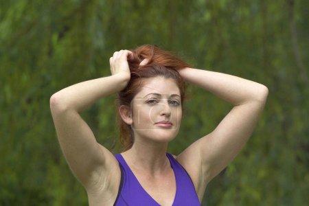 Girl holding hair in park