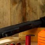 Black 12 gauge pump action shotgun with shells, cl...