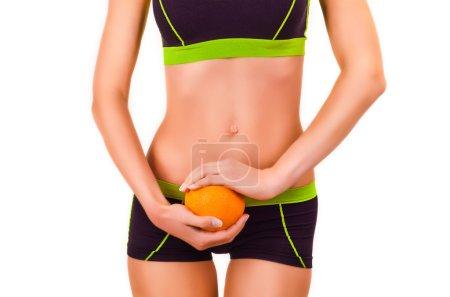 Slim figure of woman in a sportwear with orange in a hands