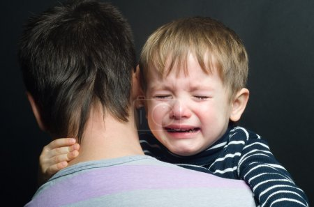 Photo for Crying child in the arms of his father - Royalty Free Image