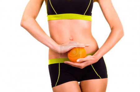 Slim figure of woman with orange in a hands