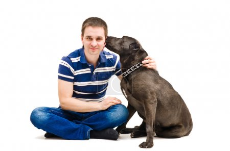 Young man and his licking dog