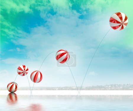Five jumping white red striped inflatable balls on beach with sea